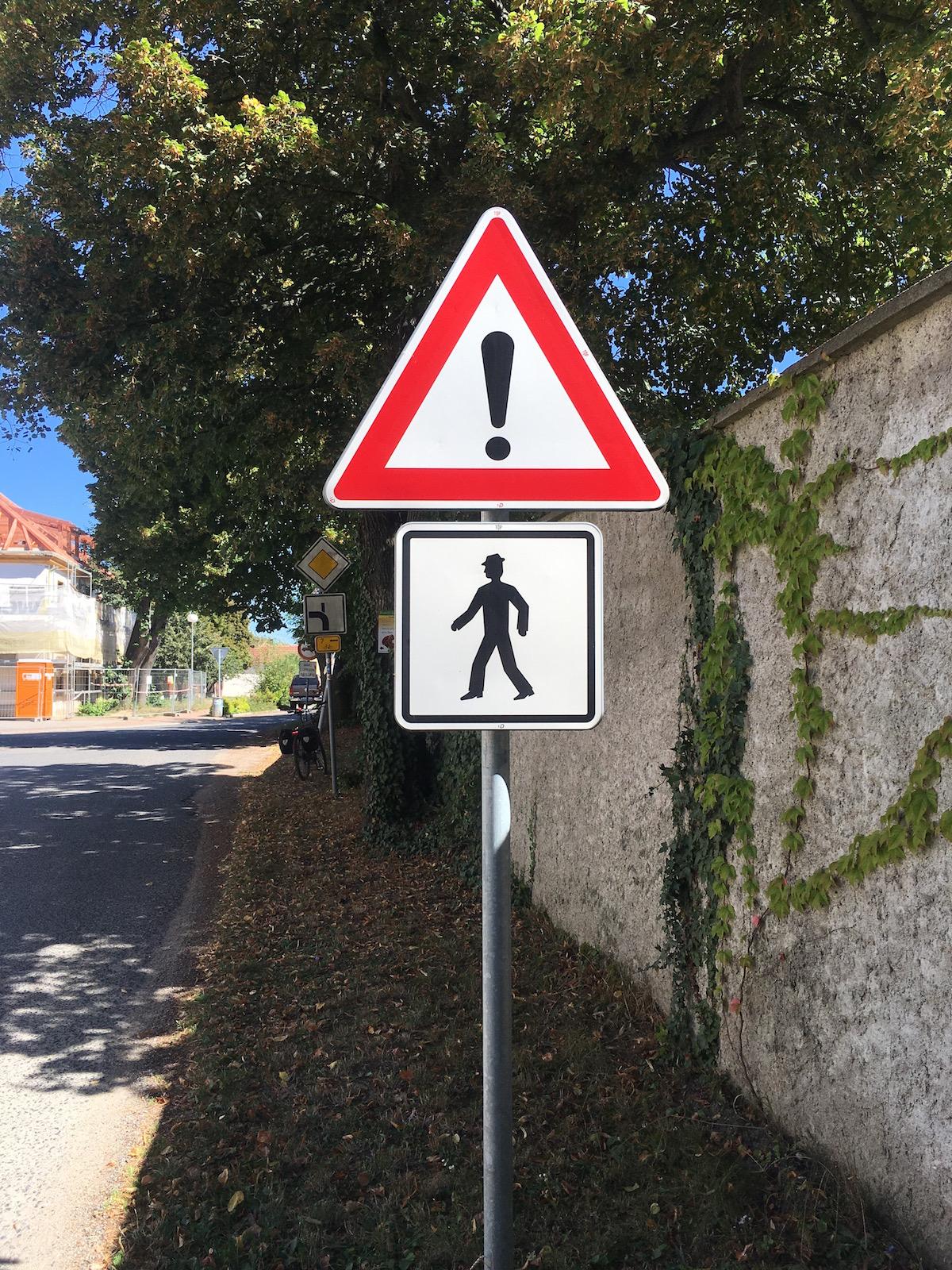 Verkehrsschild: Mann mit Warnausrufezeichen auf dem Kopf